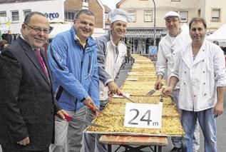 Beim Anschnitt: die drei Bäckermeister, Andreas Stein und Pfarrer Kreß