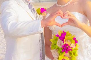 ハワイオアフ島 ビーチでウエディングドレスにブーケを持った花嫁と白いタキシードの花婿がそれぞれの手を合わせハートを型取っている