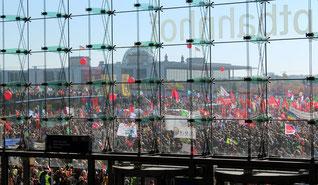 Blick durch Glasfront Hauptbahnhof auf zehntausende Demonstranten. Stopp TTIP und CETA. Großdemonstration von 250.000 in Berlin. Foto: Helga Karl am 10.Okt. 2015