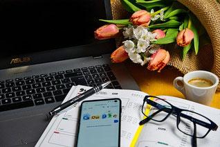 ホームオフィス。ノートパソコンと資料。スマホ、ペン、眼鏡。マグカップに入ったコーヒー。麦わら帽子に投げ込まれたピンクのチューリップ。