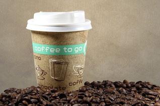 コーヒー豆にうずもれたテイクアウトコーヒーのカップ。