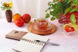 テーブルに広げられたメモ帳と万年筆。紅茶の入った耐熱ガラスのカップ&ソーサ。フルーツと観葉植物のバスケット。ひまわりが活けられた花びん。
