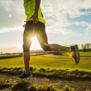 Joggender fitter Mensch auf Feldweg vor Grüner Wiese.