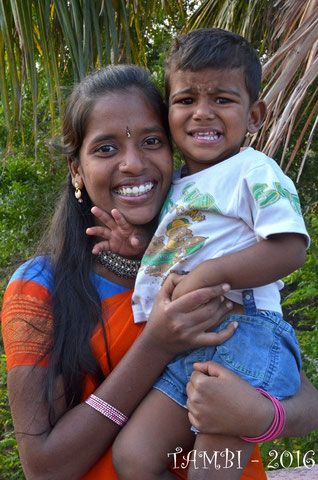 Saranya tenant un de ses petits voisins dans les bras - 2016