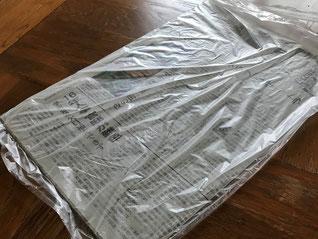 雨の日の新聞カバー。一辺をはさみでカットします