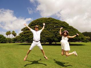 ハワイオアフ島 日本語ガイド付き貸切チャーター モアナルアガーデンのこの木なんの木のモンキーポッドの木の前で白い夏服の二人の男女がジャンプ
