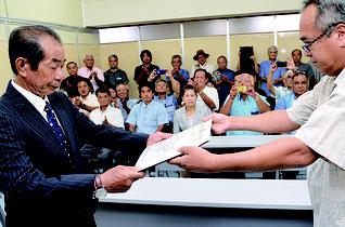 内盛委員長から当選証書を受け取った西大舛氏(左)。多くの支援者も詰めかけた=1日、竹富町役場