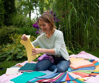 Vera Löwe sitzt vor einem Blumenbeet und hat über 100 farbiger Tücher um sich aufgefächert
