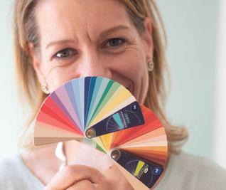 Vera Löwe hält zwei Farbfächer vor ihr Gesicht und lächelt mit den Augen