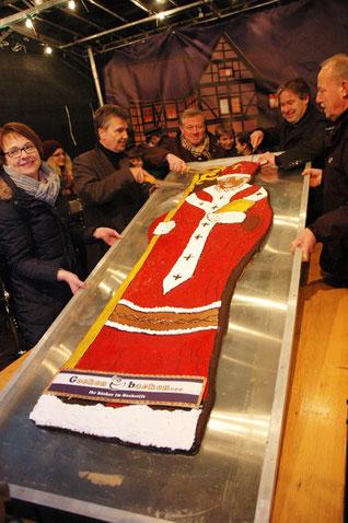 Auf einem Metallbrett liegt der große Spekulatius-Nikolaus. Von Mitarbeitern des Bonifatiuswerkes wird er mit einem Messe angeschnitten.