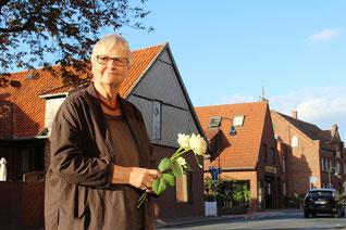 Weiße Rosen für die Opfer legt Annekatrein Kleine vom Arbeitskreis neben den Stolpersteinen ab.