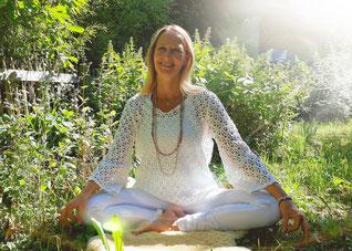Ein Mensch mit strahlend weißer Aura sitzt im Lotussitz vor einem blauem Universum. Die einzelnen Chakren leuchten farbig.