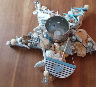 Maritimer Tischstern mit einem silbernem Metallwindlicht - dekoriert mit Fischen, Glaskugeln, Treibholz und Muscheln in weiß und blau.