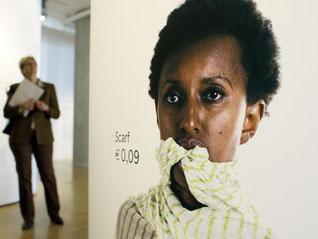 Ein Besucher neben Bildern von Anne Friesel. Die Ausstellung «Fast Fashion. Die Schattenseiten der Mode» läuft erzeit im Museum für Kunst und Gewerbe in Hamburg. Foto: Malte Christians