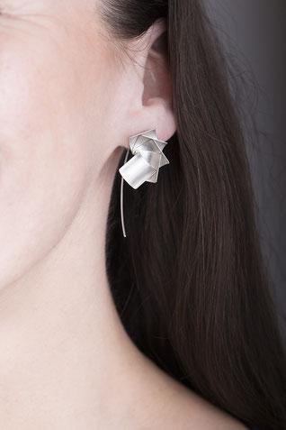 Der Ohrschmuck ALA aus Silber ist wunderbar zart und elegant. Leicht gewölbte, quadratische Plättchen aus feinstem Silber sind fächerförmig zu federleichten Ohrhängern angeordnet. Getragen wirken sie zart und fein, gleichzeitig anziehend & außergewöhnlich
