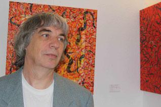 Dozent vor Ausstellungskulisse, Ölbilder in Orange und Rot, Abstrakt