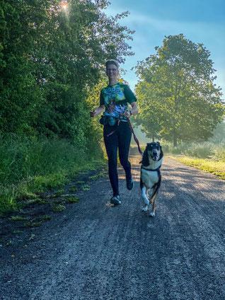 Frauchen und ich laufen auf die Kamera zu, man sieht, dass es uns Spaß macht. Frauchen trägt das Teilnehmer Tshirt in grün mit Hunden darauf..