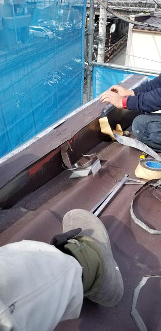 既設の笠木を切ったりして防水テープを張っている