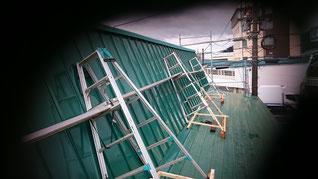 斜めの屋根に対して斜めに脚立を立てて足場を作っている