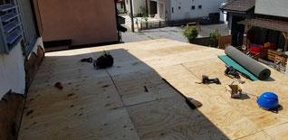 飛散した屋根をコンパネで補修している