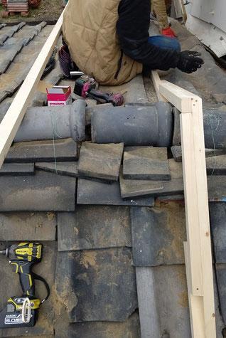 瓦屋根の上に木で骨組みを作っている。