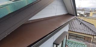 庇の屋根部分の平板型の板金を取り付けている
