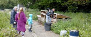 Florinel brasse le compost sous les yeux d'Olga, de Lucas et de Michelle.