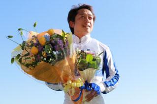 ファンからの花束を手に笑顔の藤原幹生騎手