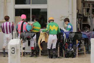 次のレースに向けて馬具を整える騎手たち