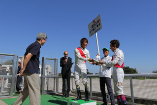 山下騎手より先に受け取った記念品を返す吉井騎手