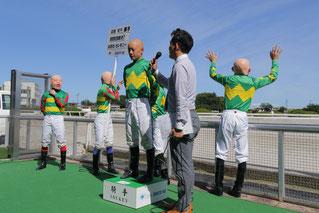 本人インタビュー中、入場した馬に手を振る落ち着きのない高橋昭平騎手2号、3号、4号