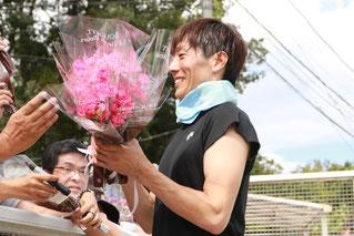 ファンに花束を配る佐藤友則騎手