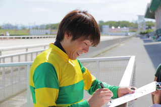 ファンひとりひとりにサインする佐藤友則騎手