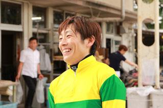 笑顔で達成時のインタビューを受ける佐藤友則騎手