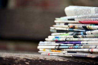 Ein Stapel von Zeitungen steht für Pressetexte wie Pressemitteilungen