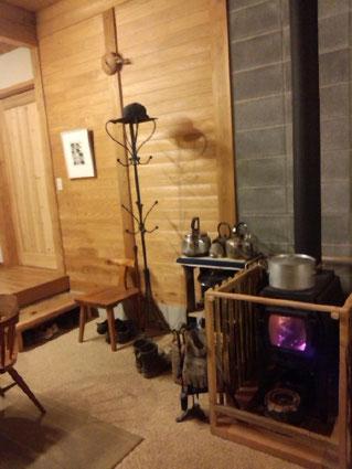 お鍋が乗った薪ストーブがいいですね~、ストーブからはパチパチ、鍋からはグツグツと音が聞こえてきそうです。 温もりのある木の壁には松本作品が。