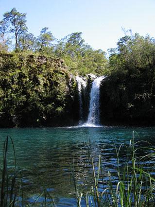 Ein Wasserfall ergießt sich zwischen üppigen Pflanzen in einen See. Das Bild symbolisiert das Element Wasser in der taloha Lomi.