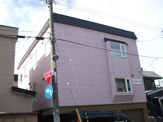 地下車庫の3階建て外壁が紫のアパートを大規模修繕する前