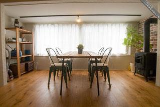 シェアハウスの、大きな窓の側に皆で集えるイスとテーブルがある風景