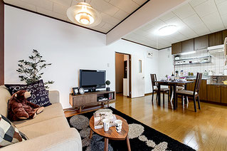 居間の隅からキッチン・ソファ・食卓テーブルが写る様に、斜め下から撮影