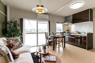 居間の奥からベランダ窓やソファ・キッチン全体が写る様に撮影