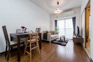 細長い居間にソファー・食卓テーブルなど家具を配置し、部屋の奥からベランダに向かって斜め下から撮影