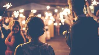 Brautpaar von Gästen mit Wunderkerzen auf ihrer Hochzeit empfangen