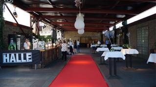 Ein roter Teppich führt durch den Sektempfang am Eingangsbereich des Biergartens