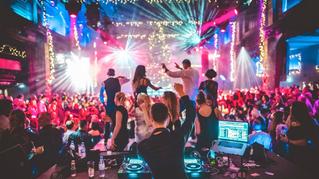 Gäste tanzen ausgelassen auf einer Erhöhung bei einer Party Veranstaltung in der HALLE Tor 2