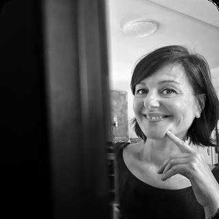 Petra Ouschan sitzt hinter einem Monitor und lächelt