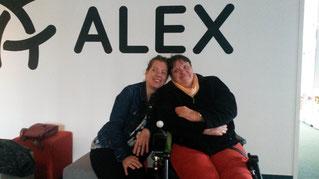 Zu sehen sind Ilka Häderle und Andrea Lauer von der Autorengruppe Aufbruch im Vorraum zum Radio Alex Berlin. Sie lehnen aneinander. Über ihnen ist groß das Logo und der Schriftzug ALEX.