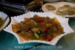 Im Vordergrund breite Reisnudeln mit geräuchertem Fleisch, im Hintergrund mit viel Zucker überdeckte frittierte Kürbiskuchen. Alles zusammen ergibt eine leckere Kombination.