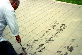 ein Kaligraphie-Künstler schreibt seine Verse auf das Pflaster