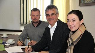 Bianca de Waal-Schneider, Peter Gefeller und Dr. Claus M. Brodersen (von rechts) unterschreiben den Vertrag. (Foto: khn)